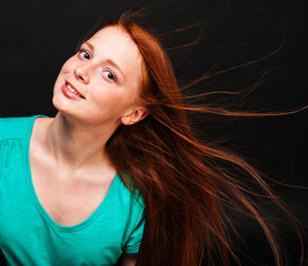 Young girl with flowing red hair on a black background