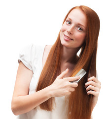 Young red-haired girl combing her long hair. Isolated on white b