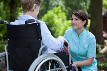 Nurse spending time with disabled woman at park