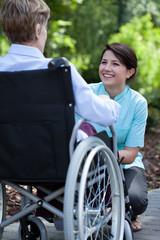 Nurse smiling to elderly woman on wheelchair