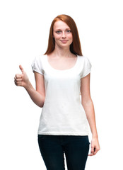Red-haired girl shows  finger on t-shirt. Isolated on white back