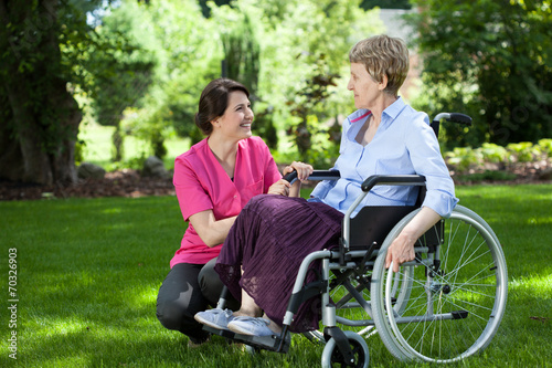 canvas print picture Senior woman on wheelchair with caring caregiver