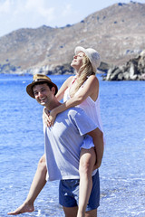 Young man is carrying her on his shoulder on the beach