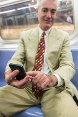 Senior Businessman Using Mobile Phone in the Subway Train