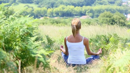 Woman in countryside doing yoga exercices