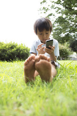 How the barefoot boy is using the mobile phone in the park
