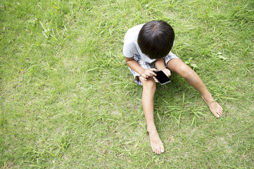 On the grass, a boy who has a mobile phone