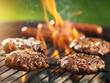 hamburgers and hotdogs cooking on flaming grill - 70329772