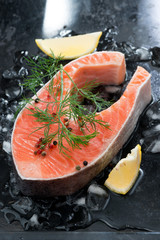raw salmon steak with dill and lemon on ice, vertical