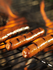 hotdogs cooking on flaming grill