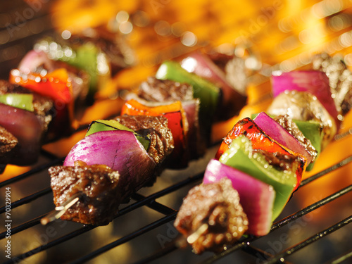 steak shishkabob skewers cooking on flaming grill - 70329904