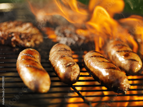 Fotobehang Barbecue bratwursts cooking on flaming grill