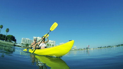 Slow Motion Young Couple Kayaking Outside In Ocean