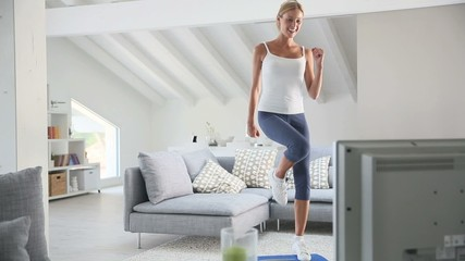 Young woman doing fitness exercises in front of TV