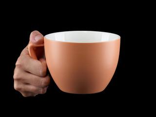 Orange - apricot color cup - mug on black background.