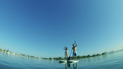 Slow Motion Couple Stand Up Paddle Surfing At Beach