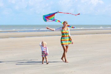 Mother and daughter flying kite on the beach