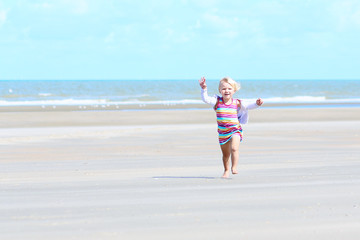 Little happy girl playing on the beach