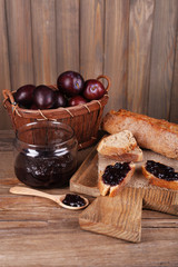 Bread with plum jam and plums on wooden table close-up