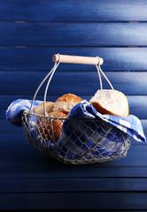 Tasty buns with sesame in wicker basket,