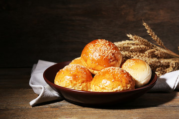 Tasty buns with sesame on plate, on wooden background