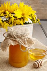 Jar of honey on wooden table, bouquet of sunflowers