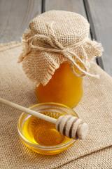 Glass bowl of honey on jute background