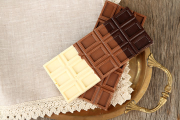 Chocolate bars on napkin, on tray, on wooden background