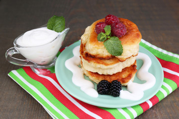 Tasty pancakes with fresh berries, cream and mint leaf