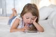 Leinwanddruck Bild - Cute Little girl using mobile phone at home