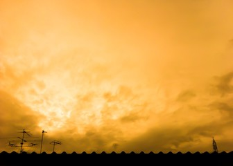 roof and antenna in silhouette. warming cloud.