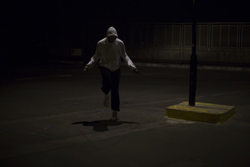 Hooded man skipping at night under a street light