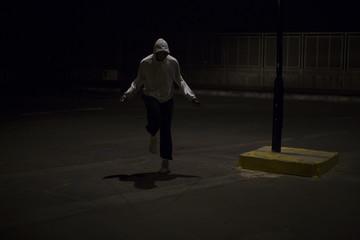 Hooded man skipping at night under a street light