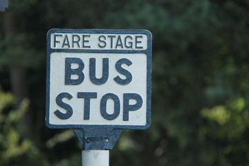A Vintage Black and White Metal Bus Stop Sign.