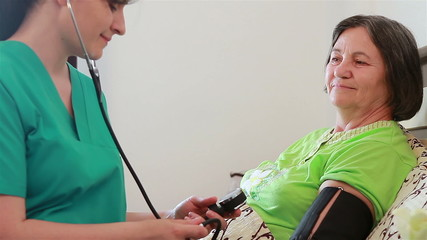 Nurse checking blood pressure to senior woman