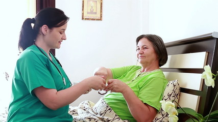 Senior woman taking medicine from nurse