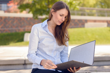 Attraktive Frau liest eine Akte in der Pause im Park