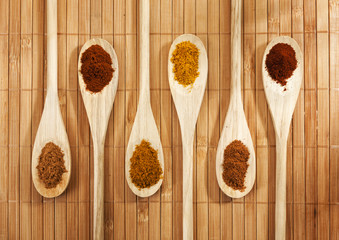 Six spices on wooden spoons