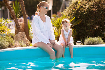 Mother and little daughter in pool
