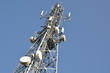 Telecommunication tower with antennas against the blue sky - 70338571