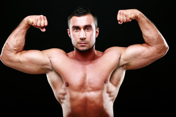 Serious muscular man showing his biceps on black background