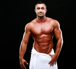 Portrait of a happy muscular man over black background