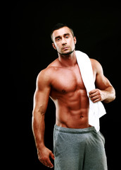 Handsome muscular man holding towel on black background