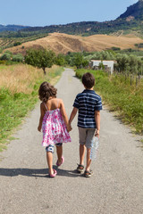 two children walking outdoor in the nature on the road