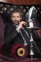 man smoking hookah at arabic restaurant.