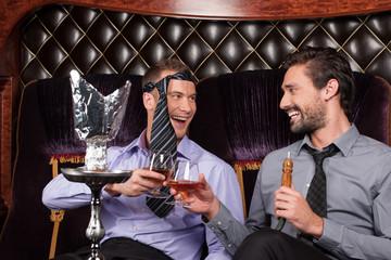 two young men smoke from shisha pipe.