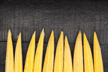 Raw sweet corns on wooden background