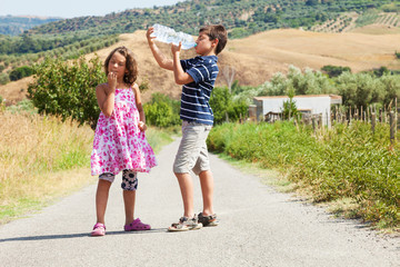 brother and sister on the road drinking water and thinking about