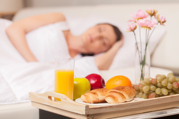 Beautiful woman with breakfast in bed early.