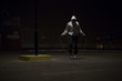 Hooded athlete skipping at night under a street light